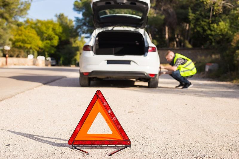 Triangle de présignalisation au premier plan suivi d'un conducteur qui répare sa voiture en second plan