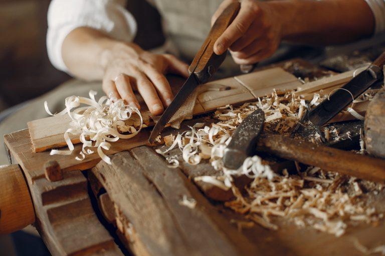 Main d'un artisan qui travaille le bois à l'aide d'outils. Trousse de secours artisan