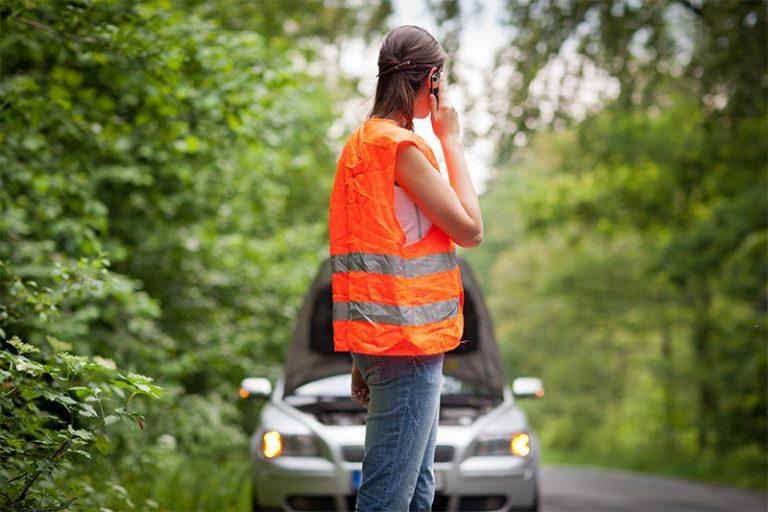 Femme portant un gilet orange fluo au bord de la route